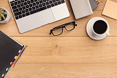Male workplace with laptop, coffee cup, notebook and glasses. Wooden background, top view, mockup, copy space.
