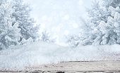 Wooden table with snowdrifts over blurred abstract winter landscape background