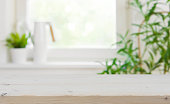 Wooden tabletop with copy space over blurred kitchen window background