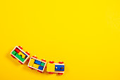 Wooden toy train with colorful blocks on yellow background. Top view