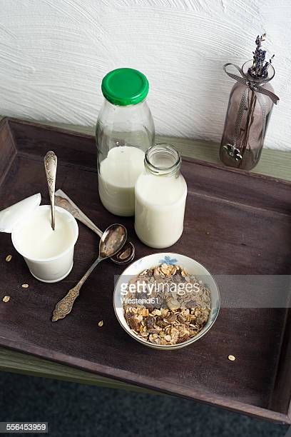Wooden tray with bowl of granola, bottles of milk and cup of natural yoghurt