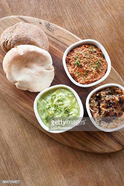 Wooden tray with pita bread and 3 hummus dips