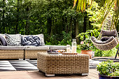 Rattan table with milk on wooden veranda with hanging chair and settee