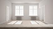 Wooden vintage table top or shelf closeup, zen mood, over blurred empty room with parquet floor, big windows, doors and radiators, white architecture interior design