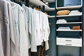 wooden wardrobe in walk in closet with clothes hanging on rail, interior design concept