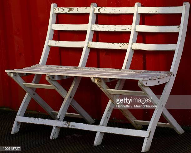 Wooden white bench on a red background