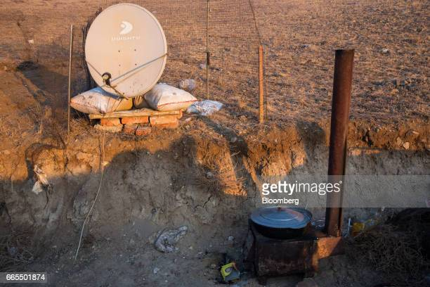 A woodfired stove sits next to a satellite dish in a ger district in Ulaanbaatar Mongolia on Tuesday March 14 2017 The subzero winters in Ulaanbaatar...