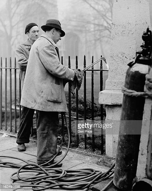 W J Woodford looks on as W Barnes uses an oxyacetylene cutter to remove railings outside Westminster Abbey London 16th January 1953 The railings are...