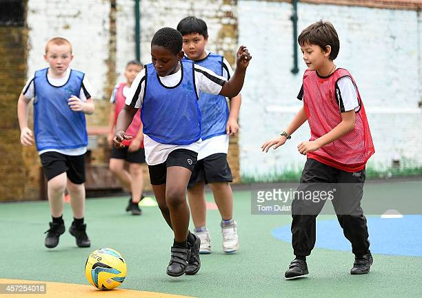 Woodhill Primary School pupils play football as they celebrate the opening of its new multiuse sports facility on October 15 2014 in Greenwich...
