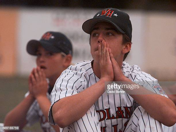 Woodland Hills players Ryan Malleus and pitcher Jimmy Roberts hold back tears as they watch the celebrations put on by their opponent Thousand Oaks...