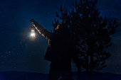 Woodman Man holding gas lamp in forest under stars at night in forest