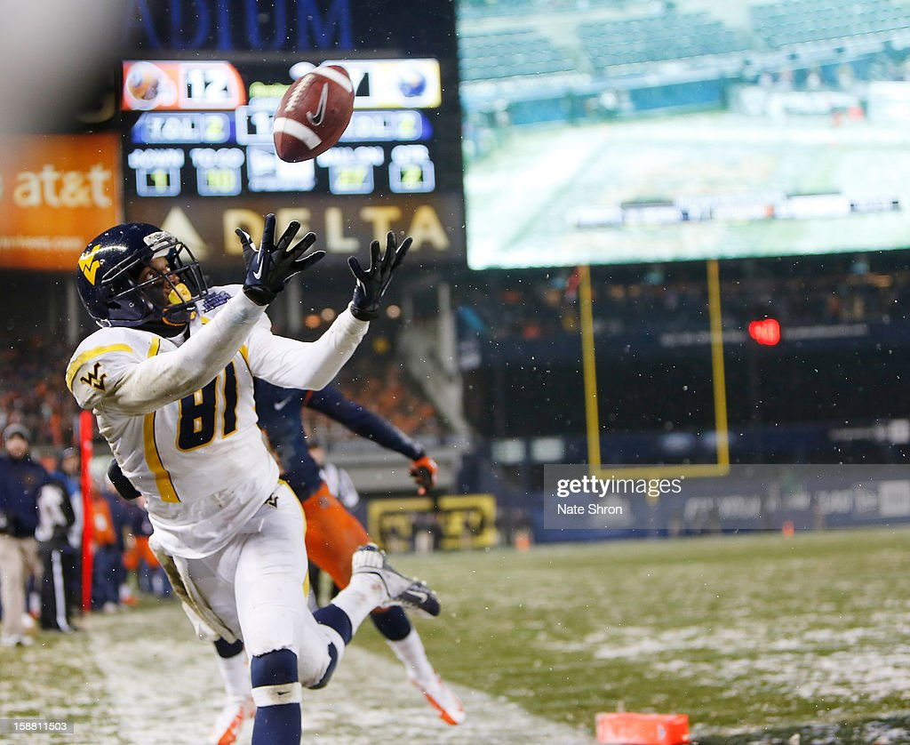J.D. Woods #81 of the West Virginia Mountaineers attempts to complete a pass aginast the Syracuse Orange during the New Era Pinstripe Bowl at Yankee Stadium on December 29, 2012 in the Bronx borough of New York City.