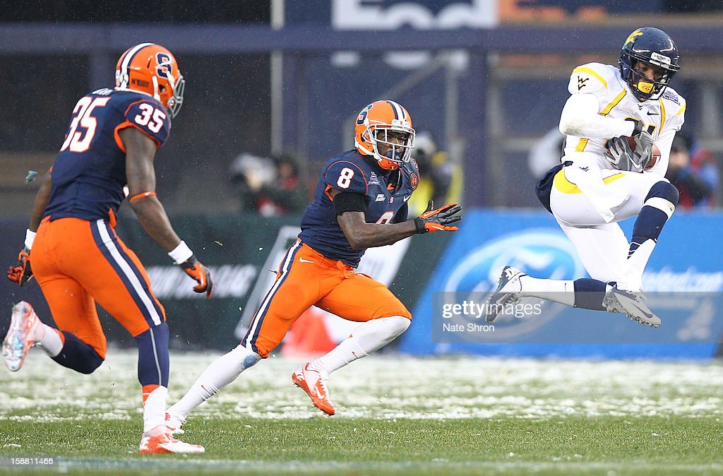 J.D. Woods #81 of the West Virginia Mountaineers completes as pass as he is chased by Keon Lyn #8 and Dyshawn Davis #25 of the Syracuse Orange during the New Era Pinstripe Bowl at Yankee Stadium on December 29, 2012 in the Bronx borough of New York City.