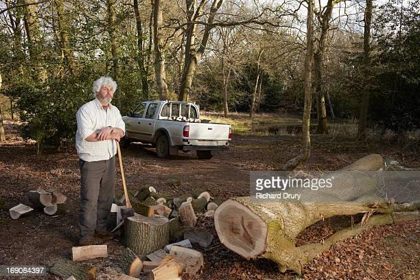 Woodsman with felled oak tree and split logs