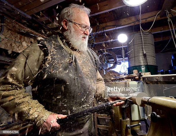 Woodworker Al Mather uses a skew chisel to remove wood spinning on a lathe as he creates a ash biscuit cutter at his home shop in China Maine