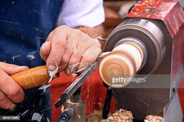 Woodworker handling gouge while working on wood with turning lathe in workshop of furniture maker