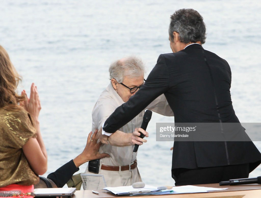 Woody Allen fall over into TV presenter Michel Denisot as he walks on stage for the Chanel+ program 'Le Grand Journal' at Majestic Beach Pier on May 12, 2011 in Cannes, France.