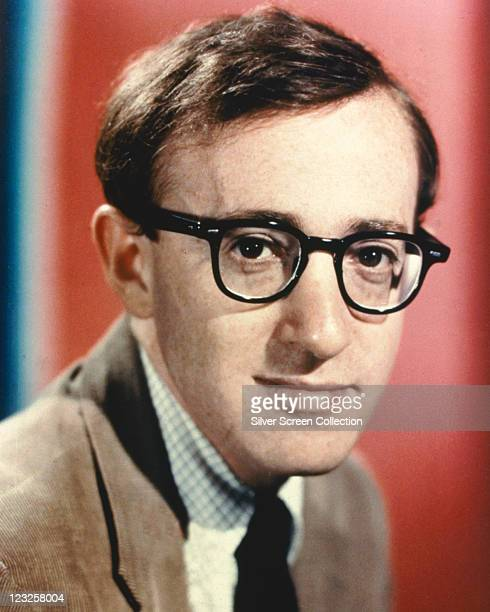 Woody Allen US comedian film director and actor wearing a brown jacket a fine check shirt and a black tie and his trademark hornrimmed spectcles...