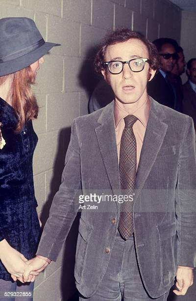 Woody Allen with Diane Keaton in a hallway with security in the background circa 1970 New York