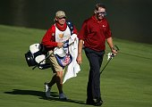 Woody Austin of the US Team walks to the 14th green wearing a dive mask alongside his caddie Brent Henley during the final day singles matches at The...