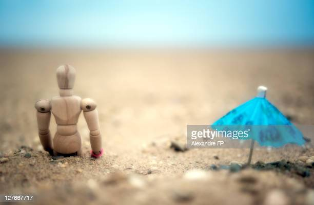 Woody manikin with blue umbrella on sandy beach