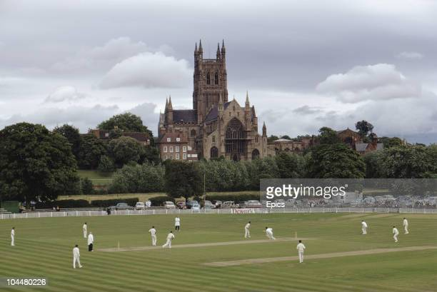 Worcester Cathedral provides the backdrop as batsman score runs in a game of cricket between Worcestershire and Sussex at Worcester country cricket...