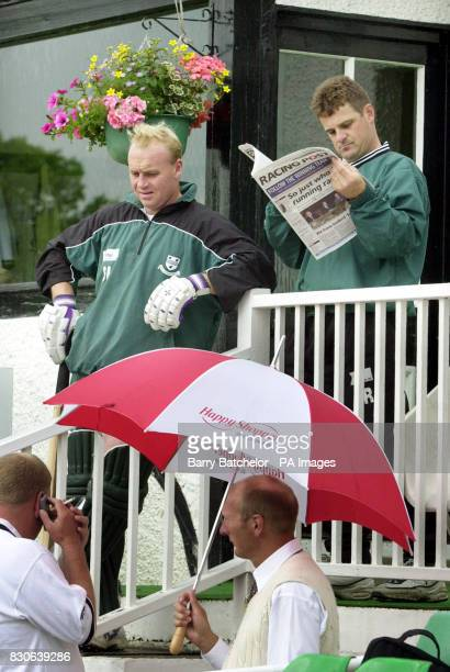 Worcestershire's Stuart Lampitt and Steve Rhodes stand waitng for the rain to stop with umpire Neil Mallender holding an umbrella during the third...