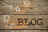 Word Blog written on vintage wooden background with knots. Wooden background with empty space.