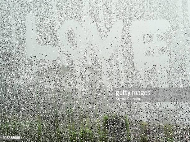 LOVE word drawing on a dewy window