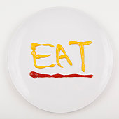 Word EAT written with mustard and ketchup