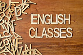Word english classes made with wooden letters on the white plank table