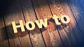 The word 'How To' is lined with gold letters on wooden planks. 3D illustration picture