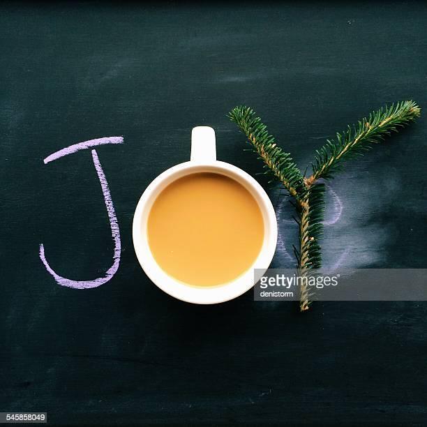 Word joy written on blackboard with coffee and fir tree branch