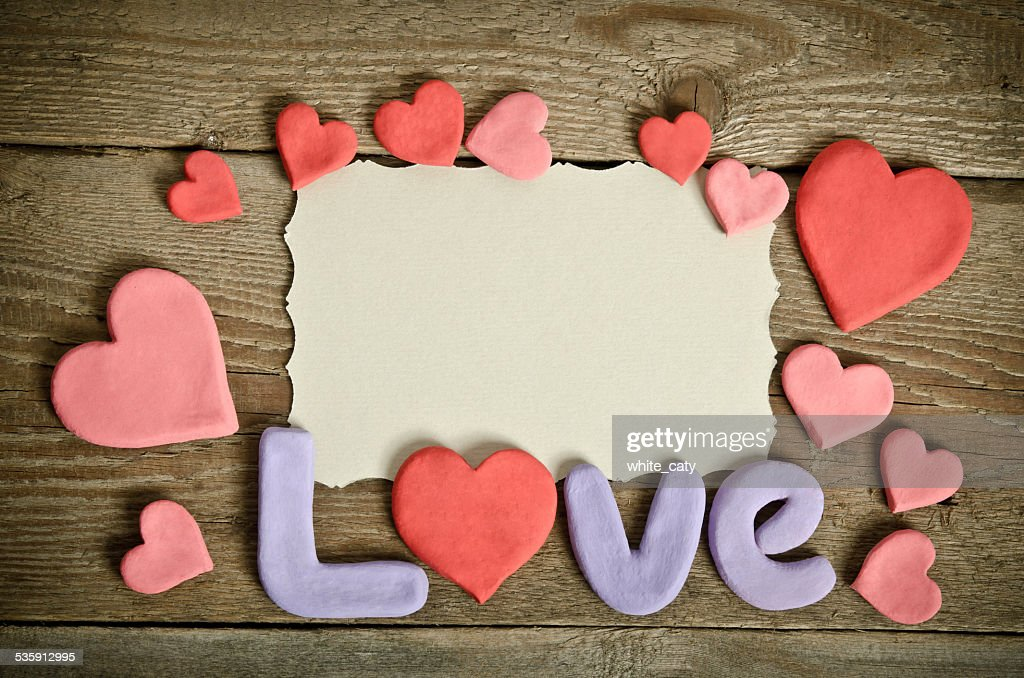 Word Love composition on the wooden board and many hearts : Stock Photo