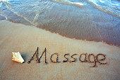 Word Massage written on the sand near the sea.Massage concept written on sand.
