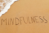 the word mindfulness written in the sand of a beach