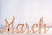 Word month of MARCH carved in wood with light background. Beginning of springtime. Spring hello concept.