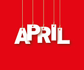 APRIL the word of the white letters hanging on the ropes on a red background