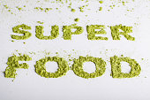 Word superfood piled of  green powder of barley grass on white background.