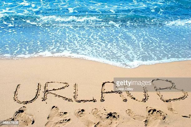 Word 'urlaub' written in sand on beach