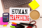 Word writing Human Trafficking in the office with surroundings such as laptop marker pen stationery coffee Business concept for Slavery Crime Prevention Workshop background space