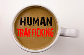 Word, writing Human Trafficking text in coffee in cup Business concept for Slavery Crime Prevention on white background with space Black text with red word