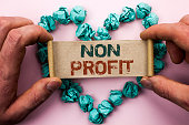 Word writing text Non Profit. Business concept for Charitable Wrothless Philanthropy Aid Unlucrative Profitless written Cardboard Paper Holding by man plain background Heart Paper Balls.
