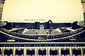 Words 'Once upon a Time' written with old typewriter on white paper in vintage style