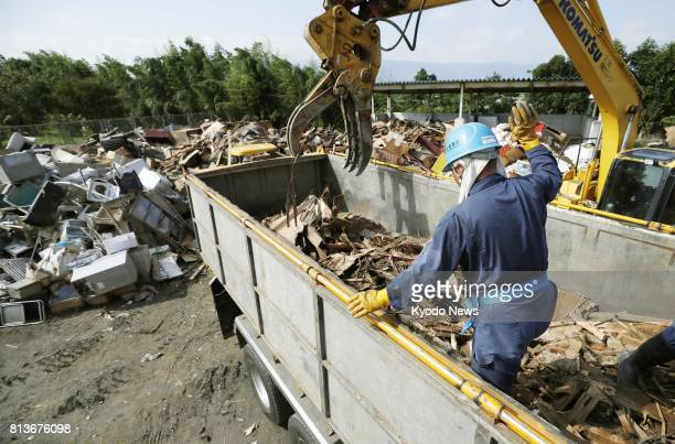 Work begins in the southwestern Japan city of Asakura in Fukuoka Prefecture on July 13 to load massive amounts of debris from days of torrential rain...