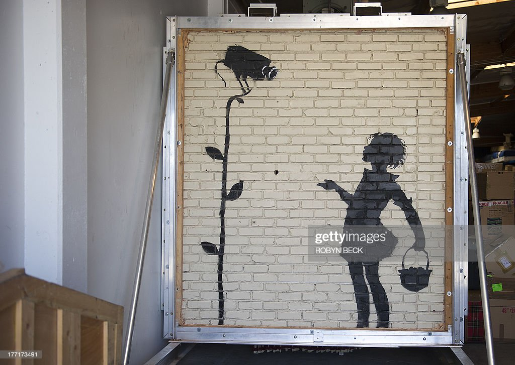 A work by Banksy titled Flower Girl is seen at Julien's warehouse in Los Angeles, California August 21, 2013. 'Flower Girl,' a 9x8 foot (2.7 x 2.4 meter) mural on brick which was originally located at a Los Angeles gas station, will headline Juliens Auctions Street Art auction in December. The owner of the gas station, before selling the property, decided to have the 9x8 foot section of the wall cut out and removed to bring it to auction. Banksy has not publicly commented on the impending sale of his art work. AFP PHOTO / Robyn Beck