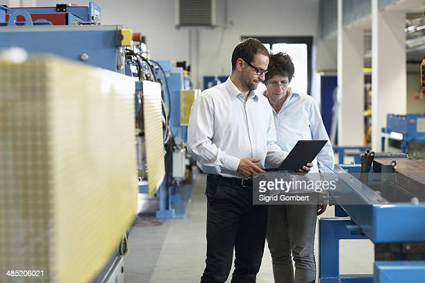Work colleagues checking information on laptop