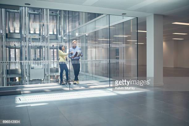Work colleagues discussing project in office hallway