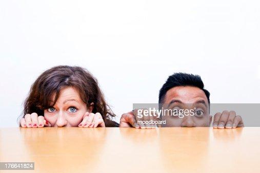 Work colleagues peeking over edge of table