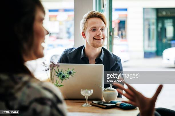 Work Colleagues Take A Break From Office To Sit Down In Cafe Together